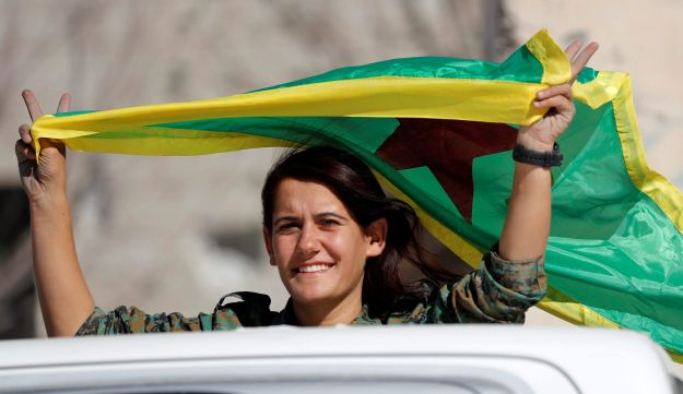A female fighter of Syrian Democratic Forces waves a flag while on board a pick-up truck in Raqqa, Syria.