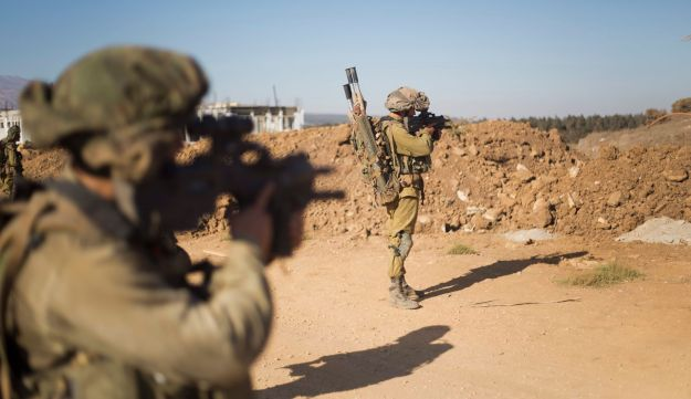 Israeli soldiers of the Golani brigade take position during training in the Israeli-controlled Golan Heights, on the border with Syria, Tuesday, Sept. 13, 2016