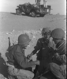 Israeli soldiers pause for a smoke while others keep watch during the Sinai Peninsula campaign, October 1956.