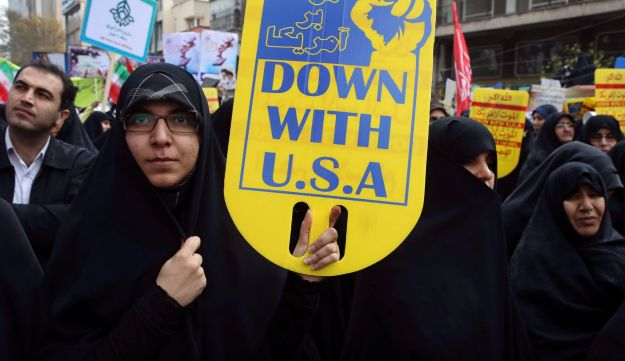 An Iranian demonstrator holds an anti-U.S. placard during an annual rally in front of the former U.S. Embassy in Tehran in 2015.