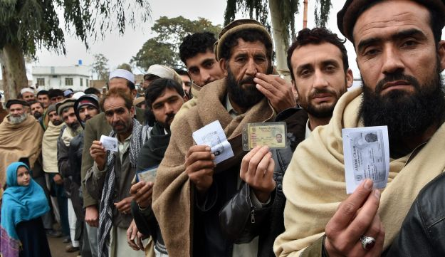 Afghan refugees wait to update their family data at the UNHCR Verification Center in Chamkani, on the outskirts of Peshawar on January 26, 2017.