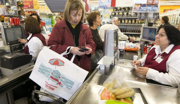 A shopper at an Israeli supermarket using a reusable bag, January 7, 2017. Faced with paying 10 agorot for a plastic bag, many are reusing bags or using trolleys.