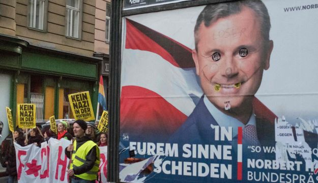 Demonstrators protest against the far-right presidential candidate Norbert Hofer, seen on an election billboard, in Vienna, Austria, December 3, 2016.