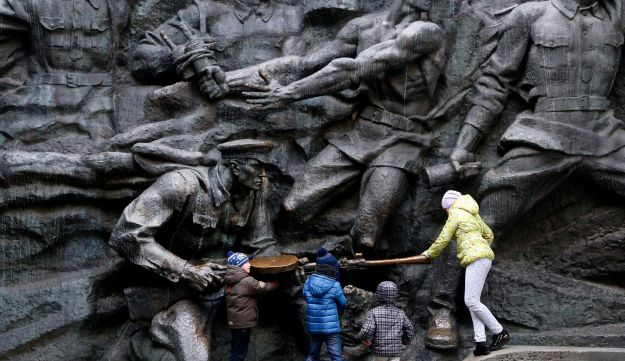 Children play at the monument of the Unknown Soldier, a memorial to World War II veterans, in a memorial park in Kiev, Ukraine. Nov. 1, 2017