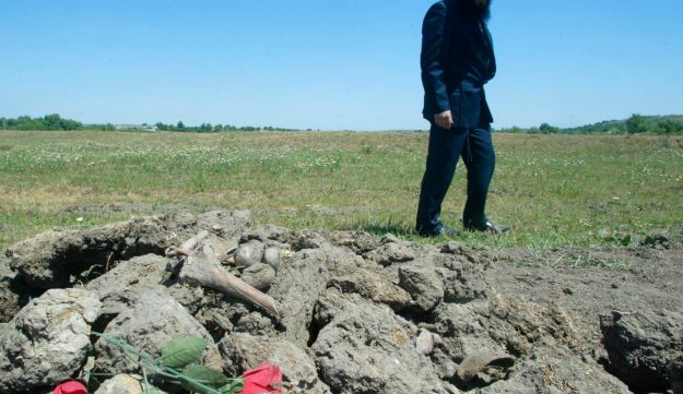 David Feldman, a rabbi from Odessa, stands at what Jewish leaders say is a mass grave of Jews slaughtered in Ukraine during World War II, in the village of Gvozdavka-1, Ukraine. June 7, 2007