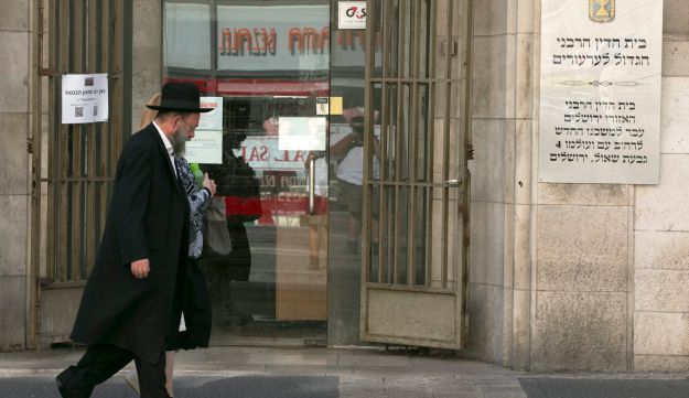 A religious couple walks past the entrance to the Jerusalem Rabbinical Court, 2014.