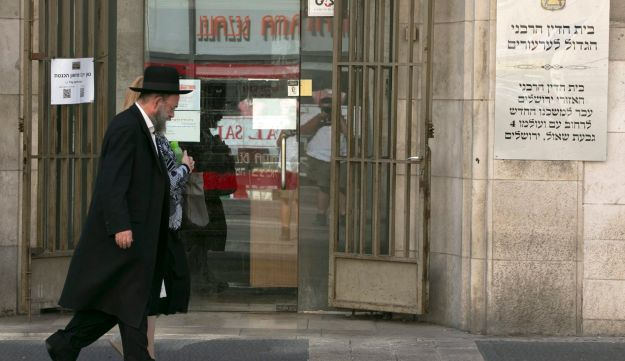 FILE PHOTO - A religious couple walks past the entrance to the Jerusalem Rabbinical Court, 2014.