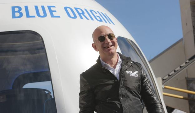 Jeff Bezos, chief executive officer of Amazon.com Inc. and founder of Blue Origin LLC, smiles while speaking at the unveiling of the Blue Origin New Shepard system during the Space Symposium in Colorado Springs, Colorado, U.S., on Wednesday, April 5, 2017. Bezos has been reinvesting money he made at Amazon since he started his space exploration company more than a decade ago, and has plans to launch paying tourists into space within two years. Photographer: Matthew Staver/Bloomberg