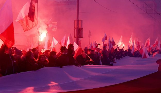 Demonstrators burn flares and wave Polish flags during the annual march to commemorate Poland's National Independence Day in Warsaw on November 11, 2017