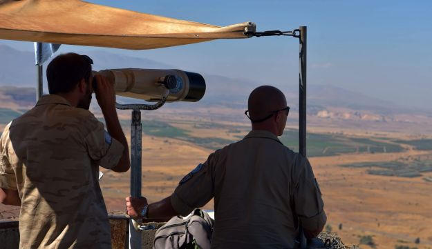 UN soldiers watch fighting in Syria on the Israeli side of the Golan Heights, September 14, 2017.