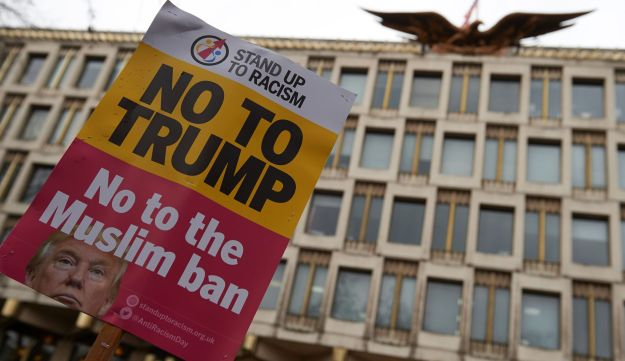 Demonstrators holding placards take part in a protest against US President Donald Trump outside the U.S. Embassy in London on February 4, 2017.