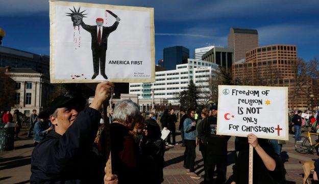 A man holds a sign depicting the cover of the German magazine Der Spiegel during a rally against Trump's executive order in Denver, Colorado, February 4, 2017.