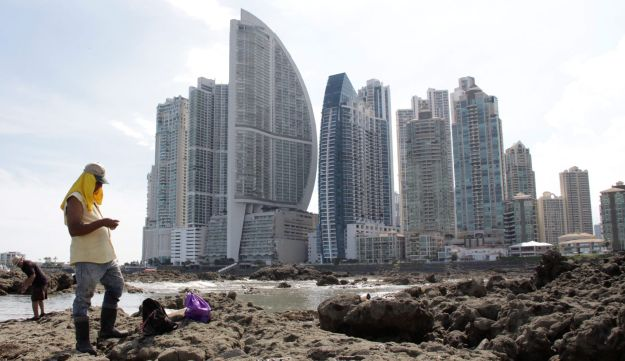 People stand on rocks on the shore during low tide as the Trump Ocean Club International Hotel and Tower Panama (3rd L) is seen next to apartment buildings in Panama City, Panama October 11, 2017.
