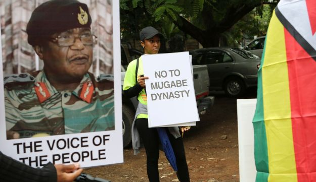Demonstrators call for the ouster of President Robert Mugabe, placed under house arrest by Zimbabwe's generals, including Constantino Chiwenga, on poster left. Nov. 18, 2017