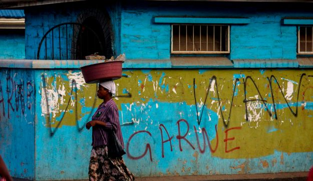 """People walk past a wall with a graffiti reading """"We want garwe"""" ['crocodile', in the Shona language), referring to sacked vice president Emmerson Mnangagwa, on November 15, 2017 in Harare, Zimbabwe"""