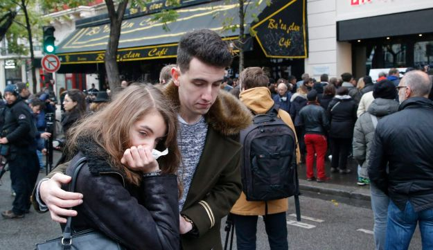People console each at the Bataclan concert hall in Paris, Sunday, Nov. 13, 2016.