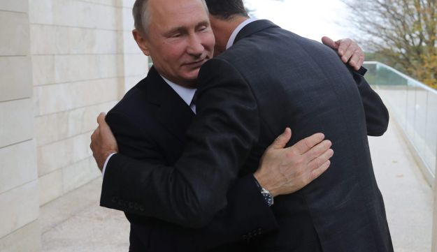 Russia's President Vladimir Putin embraces his Syrian counterpart Bashar al-Assad during a meeting in Sochi on November 20, 2017