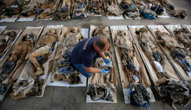 Oct. 31, 2013, file photo, Bosnian technical worker Zlatan Music examines bodies exhumed from a mass grave at the Sejkovaca identification center, near Sanski Most, Bosnia. As a U.N court prepares to hand down its verdict in the case against Ratko Mladic, the Bosnian Serb military leader during the Balkan country's 1992-5 war, the remains of numerous victims of genocide and war crimes of which he stands accused still await identification.