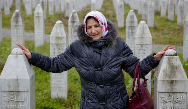 In this Thursday, Nov. 16, 2017, photo, a woman touches grave stones at the memorial center of Potocari near Srebrenica, Bosnia. As a U.N court prepares to hand down its verdict in the case against Ratko Mladic, the Bosnian Serb military leader during the Balkan country's 1992-5 war, the remains of numerous victims of genocide and war crimes of which he stands accused still await identification.