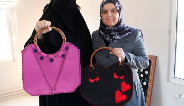 Syrian refugees Duaz, left, and Fatima showing off two of Fatima's handmade felt bags at the Women's Support Center in Islahiye, Turkey, Nov. 25, 2016.