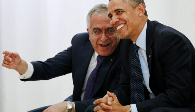 Then-U.S. President Barack Obama watches a cultural event alongside then-Palestinian Prime Minister Salam Fayyad at the Al Bireh Youth Center in Ramallah, March 21, 2013.