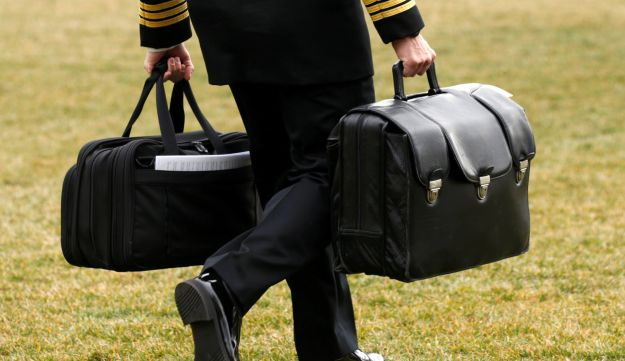 "A military aide, carrying the ""football"" containing launch codes for nuclear weapons, accompanies U.S. President Donald Trump onto Marine One upon Trump's departure from the White House in Washington, U.S. February 3, 2017."