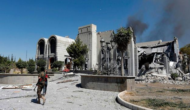 Houthi rebel fighters inspect the damage after a reported air strike carried out by the Saudi-led coalition targeted the presidential palace in the Yemeni capital Sanaa on December 5, 2017