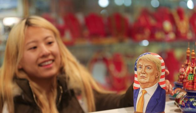 A woman looks at a martyoshka doll showing Donald Trump, U.S. president elect, in a souvenir store in Moscow, Russia, Nov. 9, 2016.