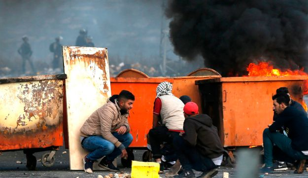 Palestinian protesters taking cover behind dust bins during clashes with Israeli troops following a demonstration against U.S. President Donald Trump's decision to recognize Jerusalem as the capital of Israel, near Beit El, December 7, 2017.