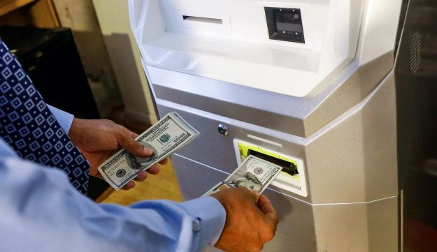 FILE PHOTO: A man feeds money into a Bitcoin ATM at the Bitcoin Center NYC in New York, U.S. on November 27, 2017.