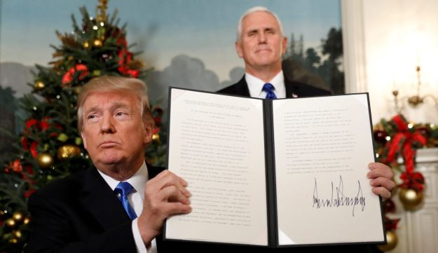 U.S. Vice President Mike Pence stands behind as U.S. President Donald Trump holds up the proclamation he signed that the United States recognizes Jerusalem as the capital of Israel and will move its embassy there, during an address from the White House in Washington, U.S., December 6, 2017.