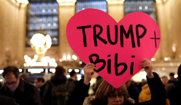 A demonstrator holds up a sign against the polices of Netanyahu and Trump at a 'Muslim and Jewish Solidarity' protest in New York, February 15, 2017.
