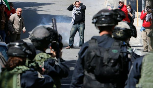 Palestinian protesters run for cover as Israeli troops fire tear gas grenades towards them during clashes at a protest in the West Bank city of Hebron February 24, 2017.