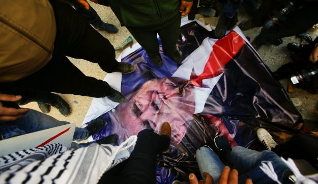 Palestinian demonstrators step on a poster depicting U.S. President Donald Trump during a protest in the West Bank city of Hebron February 24, 2017.