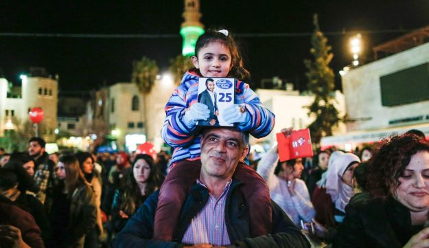 A Palestinian girl sitting on her father's shoulder poses in the biblical town of Bethlehem, amongst others in a gathering, with a picture of countryman Yaqoub Shahin, one of the finalists of the pan-Arab song contest Arab Idol, prior to the announcement of the winner on February 25, 2017.
