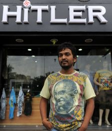 Rajesh Shah, one of the Indian owners of the Hitler clothing store poses in a t-shirt adorned with an image of Mahatma Gandhi, in front of his shop in Ahmedabad, August 28, 2012.