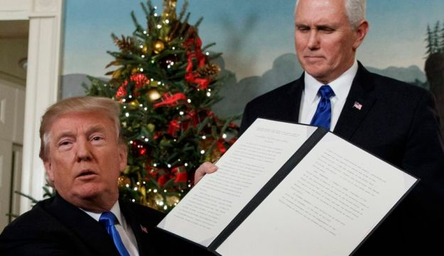 Donald Trump, with Vice President Mike Pence on hand, holding up the proclamation recognizing Jerusalem as Israel's capital, December 6, 2017.