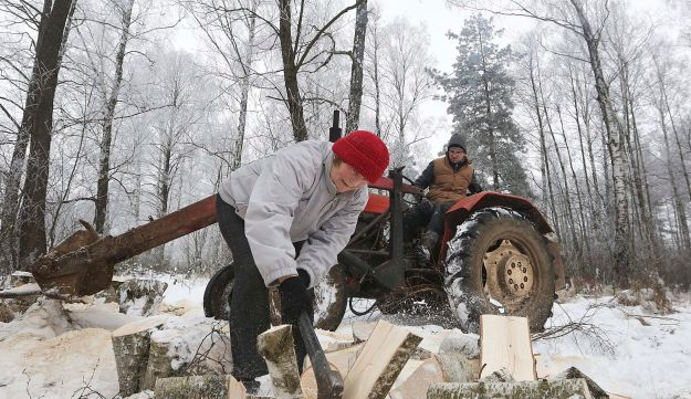 Leszek Mezynski, background, looks at his wife Jadwiga as she cuts firewood, in Kobylin-Borzymy, eastern Poland, Feb. 14, 2017.