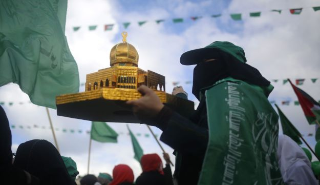 A Hamas supporter holding a miniature replica of the Dome of the Rock as she takes part in a rally marking the 30th anniversary of the founding of the Islamist movement, in Gaza City, on December 14, 2017.