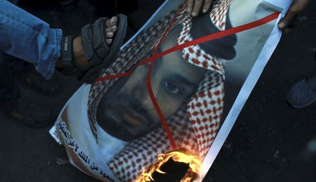 Palestinians burn a photo of Saudi Crown Prince Mohammed bin Salman during a protest against U.S. President Donald Trump's decision to recognize Jerusalem as Israel's capital, in Gaza City, Saturday, Dec. 9, 2017