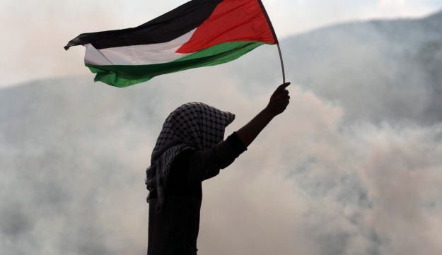 A protester waves a Palestinian flag amid tear gas fumes during clashes with Israeli security forces near the Huwara checkpoint, south of Nablus in the Israeli-occupied West Bank. December 15, 2017