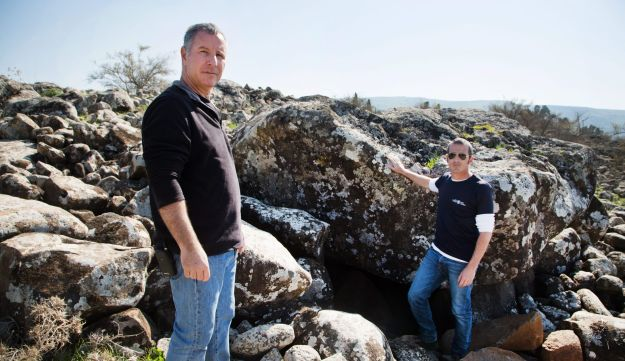 Dr. Gonen Sharon, left, with Uri Berger and the giant dolmen found in the Galilee, which uniquely for the region, has carving on its ceiling.