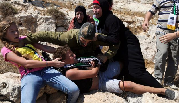 August 28, 2015: Palestinian women and youth scuffle with an Israeli soldier in the West Bank. Tamimi is seen on the left.