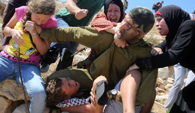 August 28, 2015: Palestinian women and youth scuffle with an Israeli soldier in the West Bank.