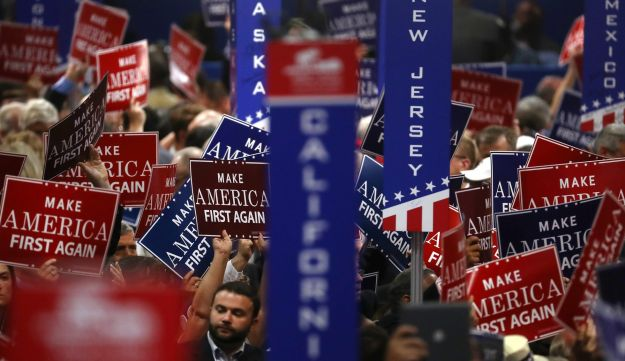 "Delegates hold signs reading ""Make America First Again"" during the Republican National Convention (RNC) in Cleveland, Ohio, U.S., on Wednesday, July 20, 2016."