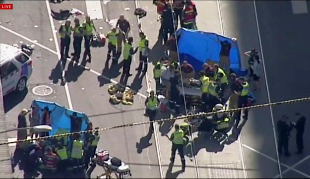 In this photo made video from the Australian Broadcasting Corp., emergency medical workers offer aid to victims struck by a vehicle, Thursday, Dec. 21, 20217, in Melbourne, Australia. Local media say over a dozen people have been injured after a car drove into pedestrians on a sidewalk in central Melbourne.