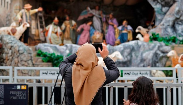 A Muslim woman takes a picture of the Christmas manger placed on the Manger Square near the Church of the Nativity in the West Bank city of Bethlehem, on December 21, 2017.