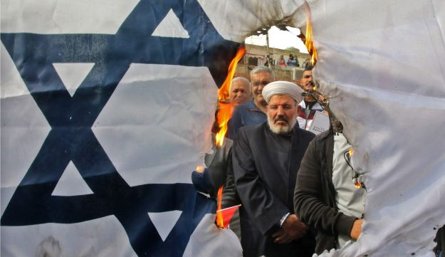 Protesters burn an Israeli flag during a Hezbollah demonstration in the southern Lebanese port city of Sidon on December 22, 2017