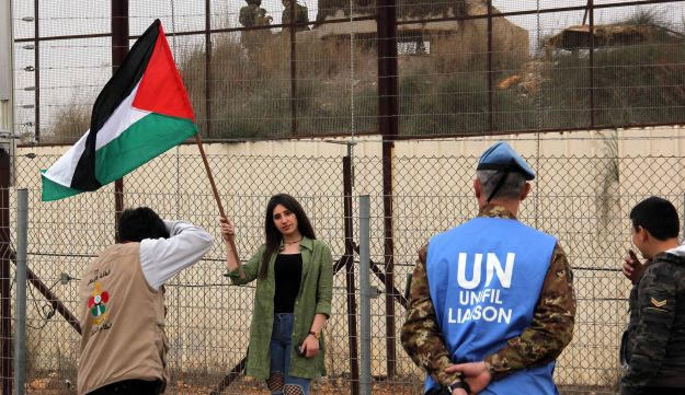 FILE PHOTO: A Lebanese girl poses for a picture with the Palestinian flag