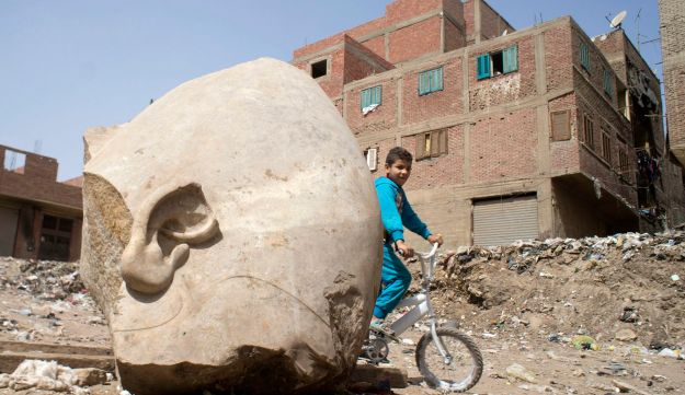 A boy rides his his bicycle past a recently discovered statue in a Cairo slum that may be of pharaoh Ramses II, in Cairo, Egypt, Friday, March 10, 2017.